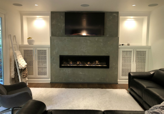 Modern living room with gray cement hearth and black linear fireplace