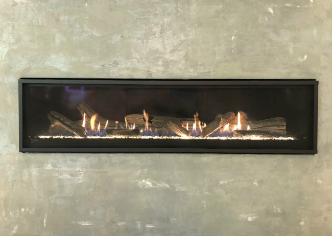Black linear fireplace with glowing fire, crystal fire glass, and driftwood logs in a cement hearth