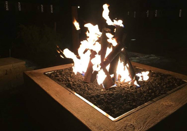 Close-up of gas logs burning on a gas fire pit at nighttime