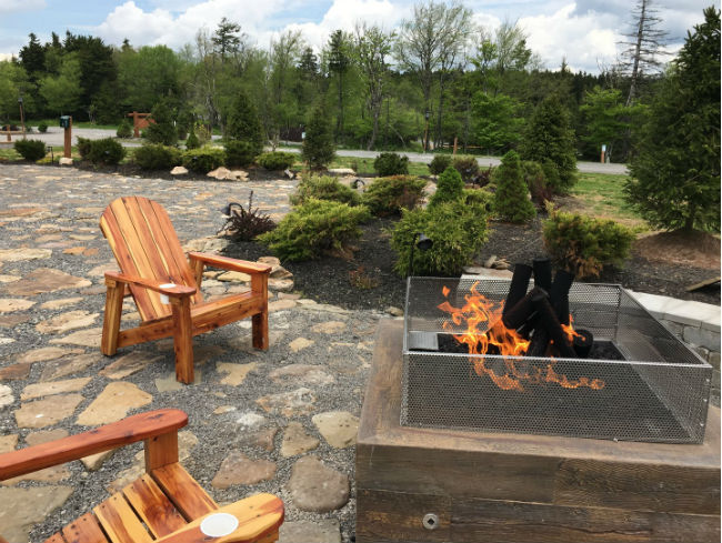 Close-up of gas fire pit and two adirondack chairs on a stone patio with a garden in the background