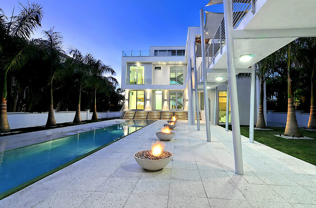 Stone patio with five gas fire bowls next to a swimming pool at an ultramodern luxury home