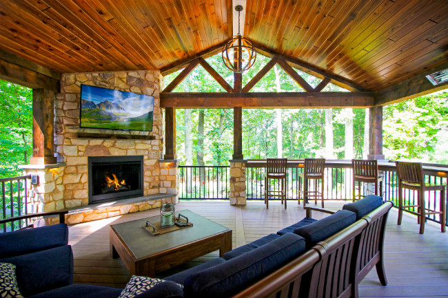 Rustic covered wood deck with outdoor living room and fireplace