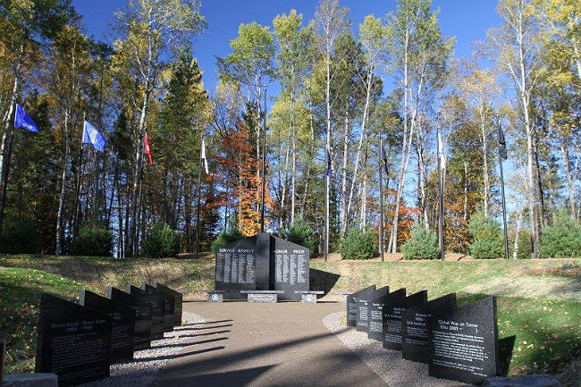 Pathway to gray granite veteran memorial in the woods