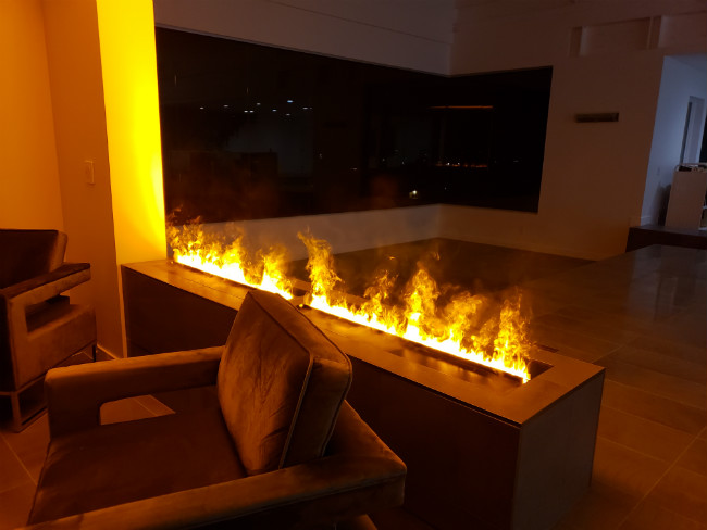 A chair in front of an OptiMyst fireplace in a dark living room
