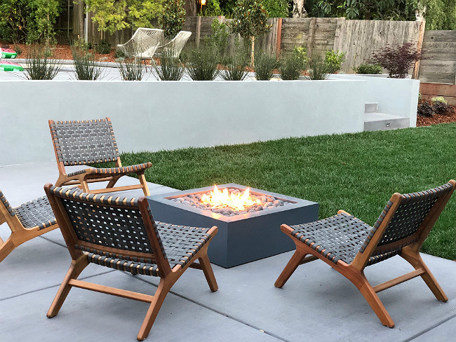 Modern gray square fire pit with four gray chairs surrounding it