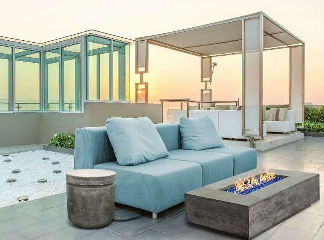 Outdoor patio with blue couch, gray concrete fire pit, and gray concrete side table