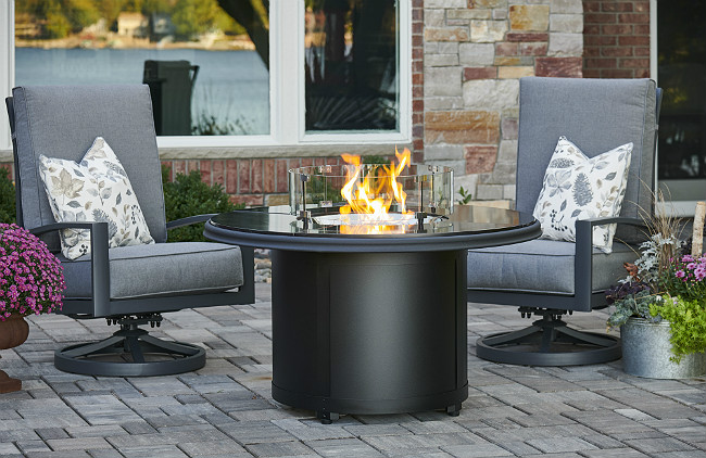 Round black fire pit on patio with two gray chairs on either side