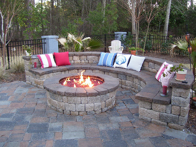 Stone masonry fire pit with lava rock inside and a stone bench surround