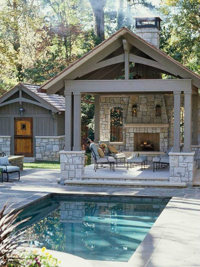 Covered outdoor living room with masonry fireplace adjacent to swimming pool