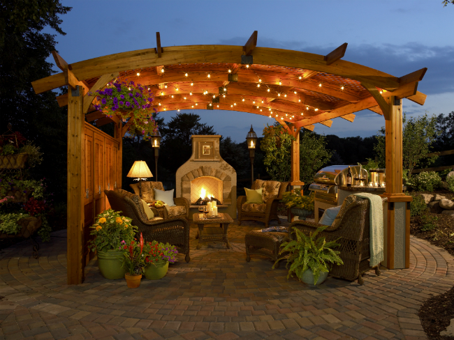 Evening view of backyard patio with gas fireplace and pergola