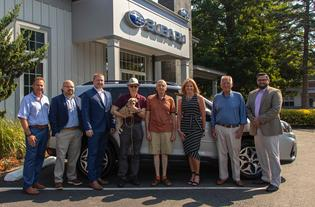 Subaru of America sells two-millionth Forester in the U.S. (L to R) Scott Hutchins (CFO), Joe Monaco (sales & marketing director), Chris Peterson (sales consultant), Brian Gerber (new Forester owner), John Reeser (customer), Kristin Hutchins (retailer president), Lewis Ruge (founder), Chris Sherman (sales manager)