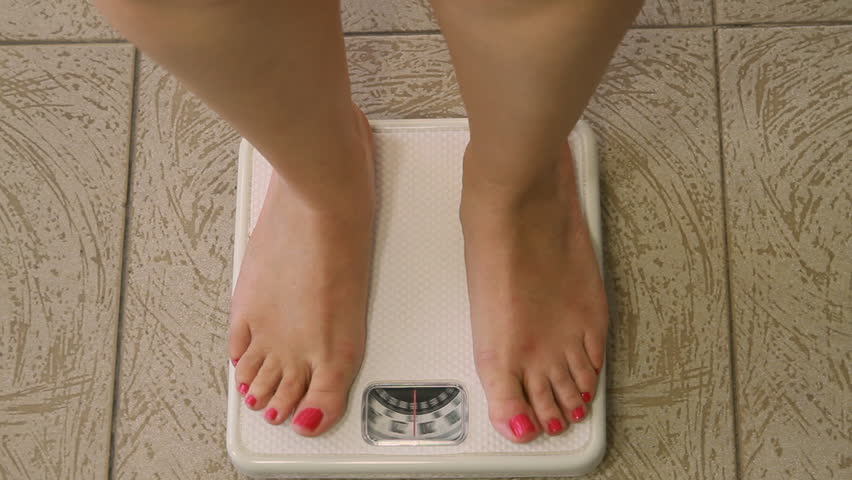 woman standing on weighing machine