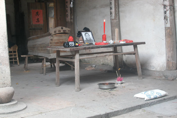 view of coffin, offering table, incense and kneeling mat