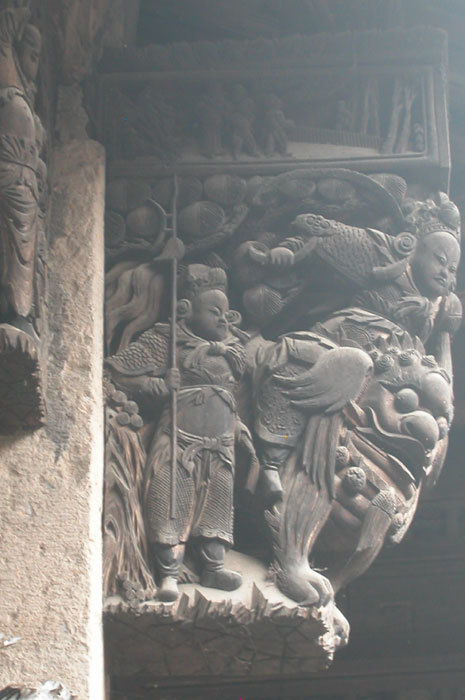 man on mythical beast; wooden bas relief