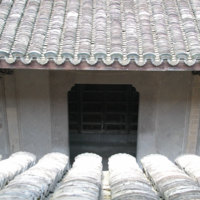 Hall entrance door viewed from central upper window showing tiles and pillar carving