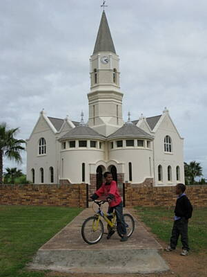 kids riding bikes in front of a church in australia