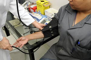 woman getting her blood pressure checked at a medical clinic