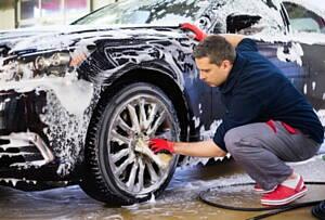 operario lavando un coche en un centro de lavado de coches