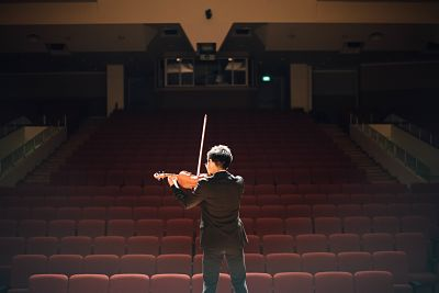 Man playing the violin in an empty auditorium