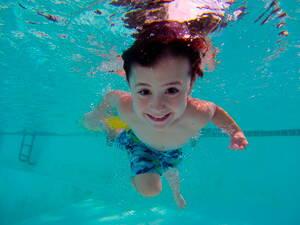 Niño en alberca practicando natación