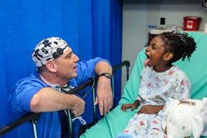 Médico especialista en pediatría atendiendo a una niña.