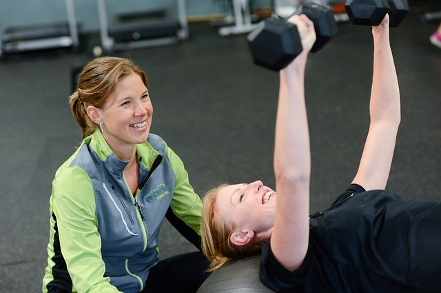 personal trainer helping a girl while working out