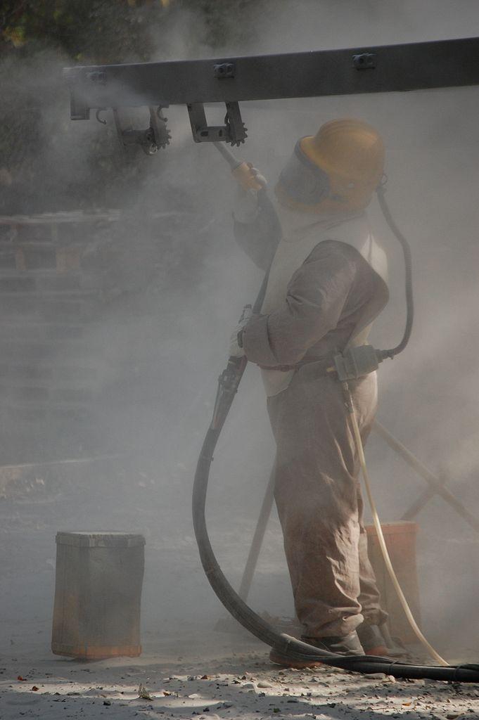man sandblasting on a machine