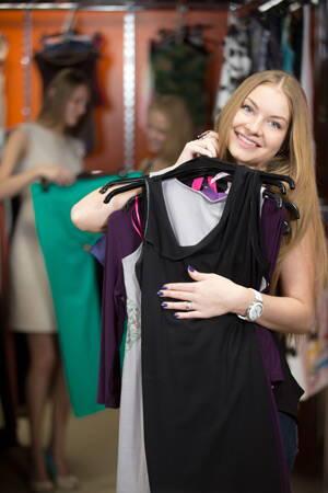 Joven en tienda de ropa eligiendo vestidos