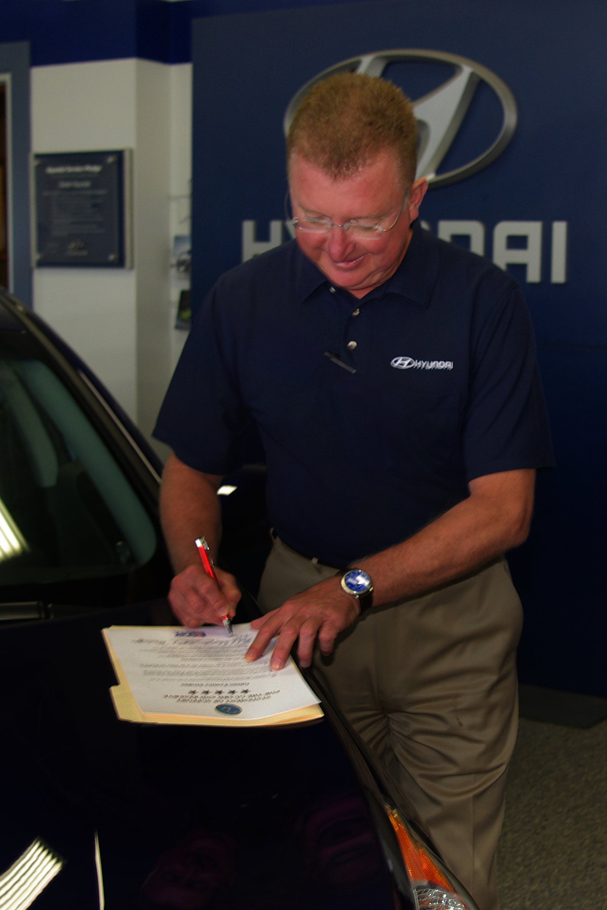 Mike Quimby Of Green Hyundai Signs An ESGR Statement Of Support Sept. 13 On  The Hood Of One Of The Cars On Showroom Floor Of The Springfield Dealership.