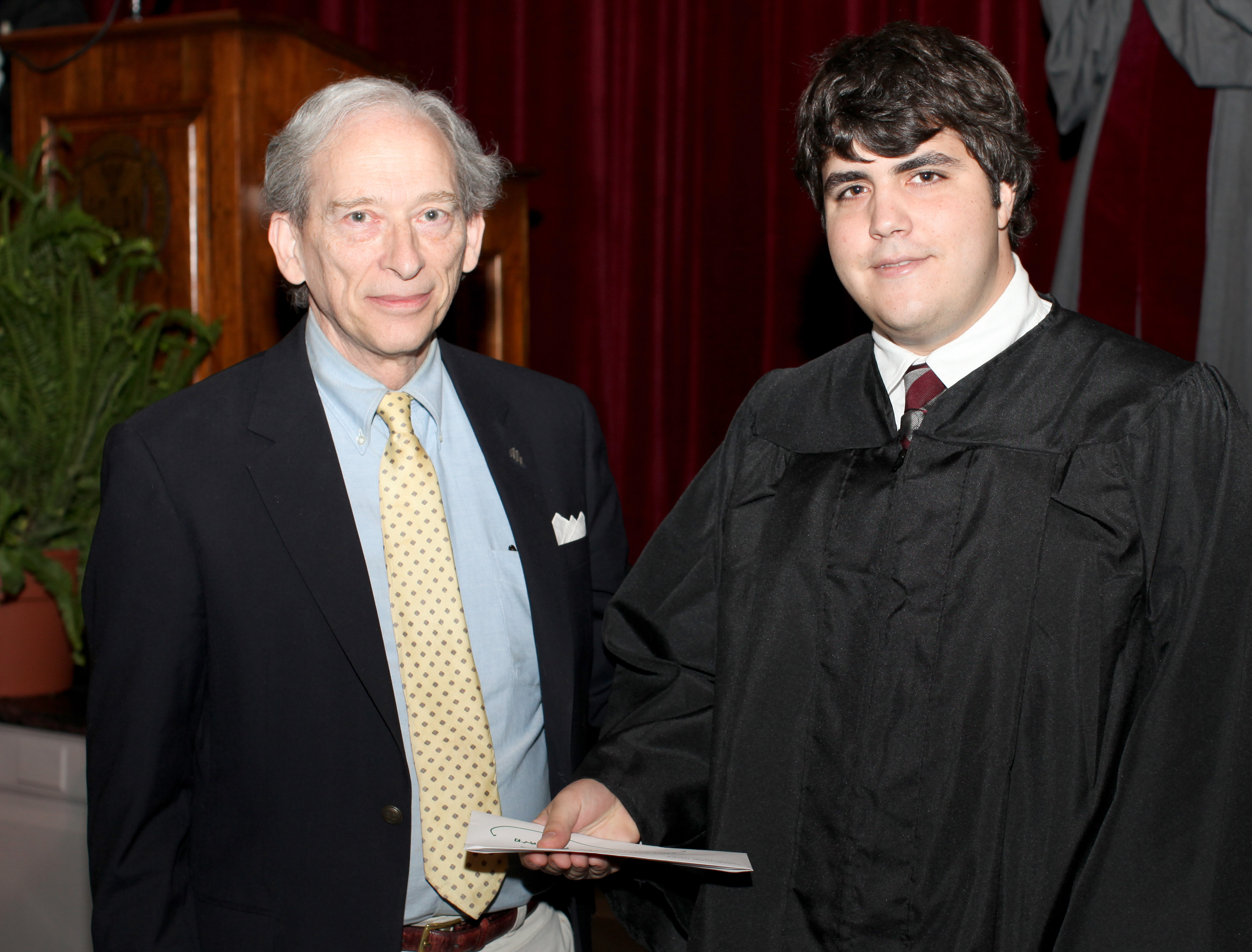 Dr. Richard McClintock giving an award to a student on the right.