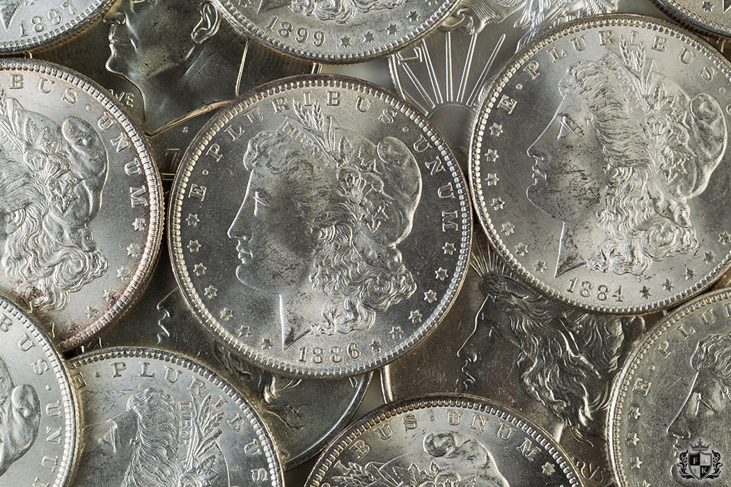 Closeup horizontal photo of several United States Silver Dollars, obverse side up, piled up