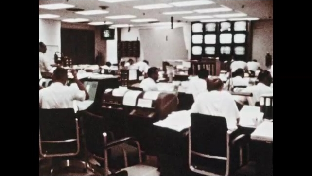 1960s: Room of space engineers at their control room computers. Measurement tool traces graph line.
