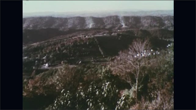 UNITED STATES 1970s – A white cloud of smoke indicates fire in a mountainside.