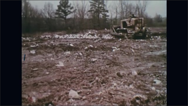 UNITED STATES 1970s – Trucks flatten garbage to make its landfill more sanitary.