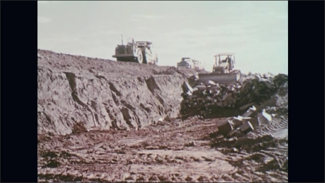 UNITED STATES 1970s – A truck brings trash to the landfill as a bulldozer pushes it into a man-made hole.