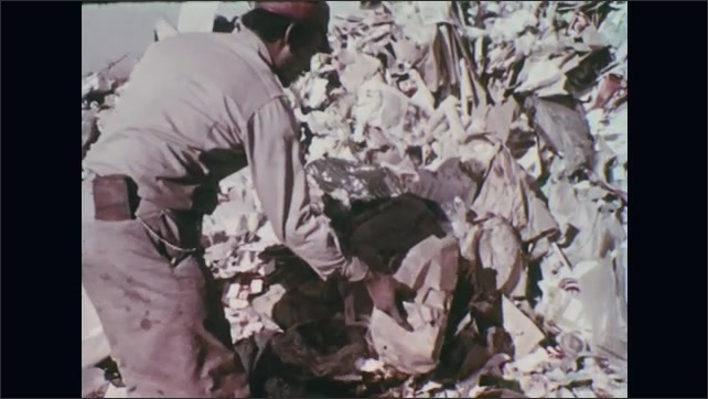 UNITED STATES 1970s – A man places a burning trash bag into a mound to burn the waste at a dumpsite.