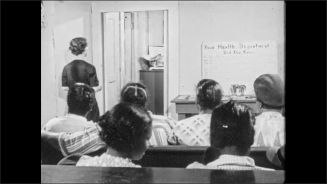 1950s: Woman puts arm around young woman. Women sit in busy clinic. Health officer and doctor consult papers and speak.