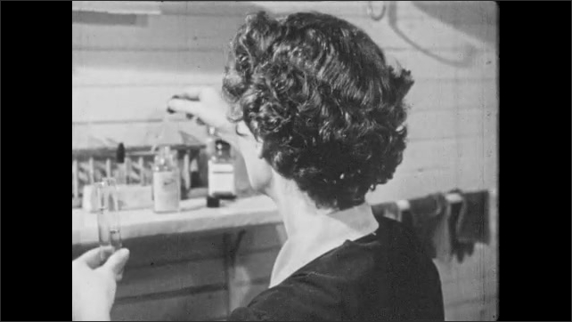 1950s: Hand squeezes blood from needle into vial. Nurse pours urine from bottle into vials. Woman enters doorway and speaks to patient. Woman puts arm around patient and speaks.
