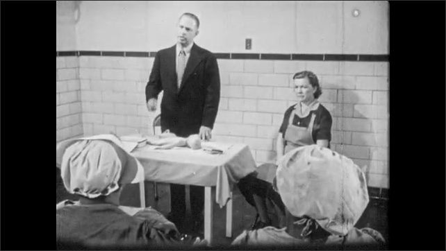 1950s: Midwives sit in classroom. Doctor stands at table with medical dummy and speaks. Midwives look concerned. Doctor stands behind table and speaks.