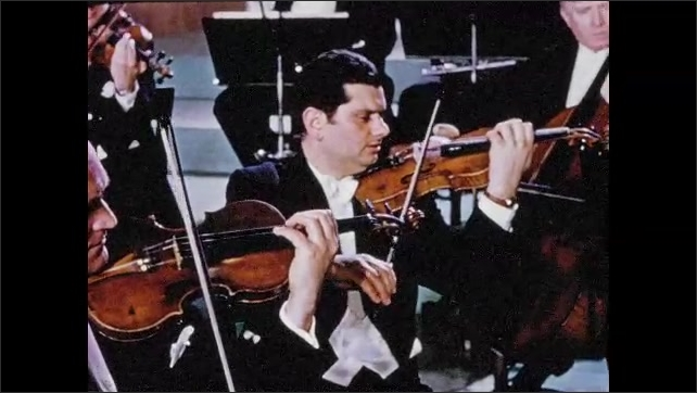 1950s: Two men playing violin in orchestra. Two men playing cellos in orchestra.