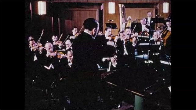 1950s: String section in orchestra plays. Man conducts orchestra.
