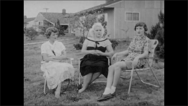 1950s: Three women sit on lawn chairs. Woman sitting on the right responds to interview questions about all white communities.