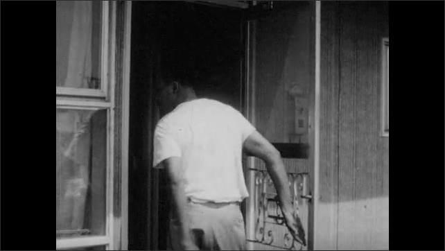 1950s: Children play in driveway. Black man puts garden hose away and walks into house while looking over his shoulder.