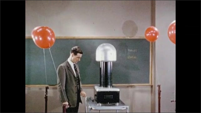 1950s: Man stands next to electrostatic machine, talks. Man operates machine, balloons tied to posts around machine lean in towards machine.