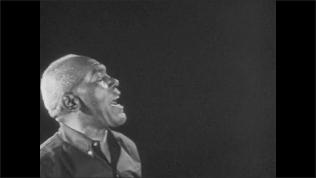 1960s: UNITED STATES: man sings. Band crouch and sing. Lady plays tambourine. Man dances.
