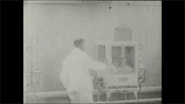 1910s: UNITED STATES: Mrs. Edison visits baby incubators at fair. Nurse attends to baby.