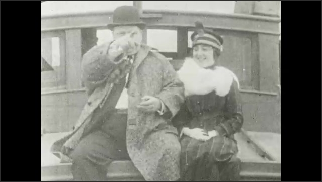 1910s: UNITED STATES: Fatty Arbuckle attends exposition. Lady and man sit on boat.
