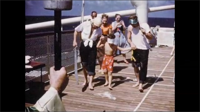 1950s: Man and woman blindfolded on ship deck, people remove blindfolds. Men walk with boy in blindfold. People in dining room.
