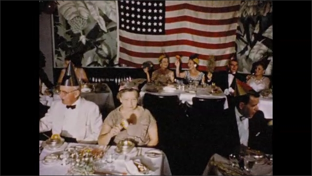 1950s: People seated at table. Pan across dining room, people waving noisemakers. People at tables.