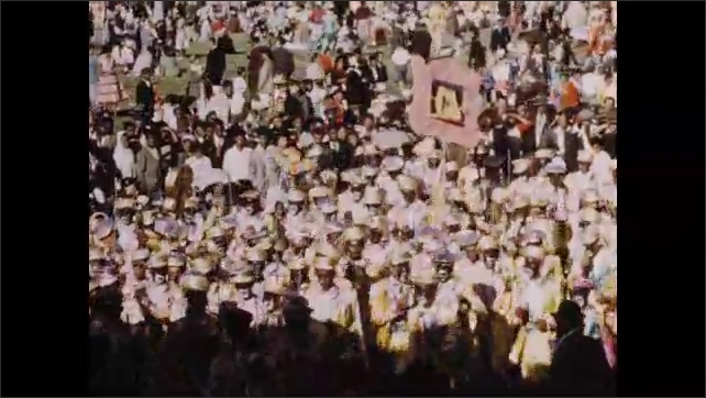 1950s: Crowd of people wearying yellow suits and blackface. Crowd of people march down road in parade.